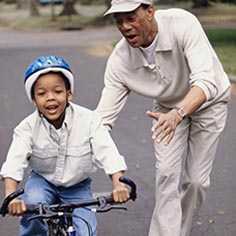 Man teaching young boy to ride a bike