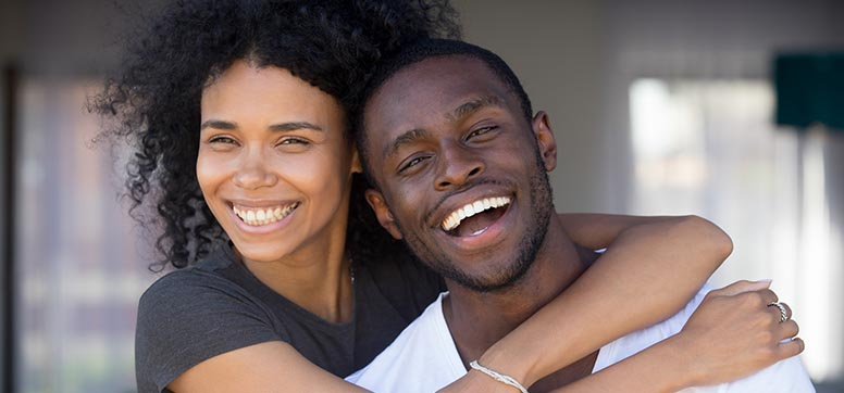 Couple embracing and smiling at the camera.